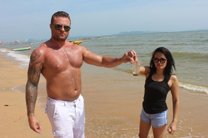 สองนักท่องเที่ยวชาวไทยและต่าง ชาติ นำแก้วน้ำพลาสติกใส ตักน้ำให้ดู มั่นใจน้ำทะเลชายหาดจอมเทียนอยู่ในเกนณ์ที่ใช้ได้