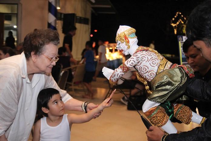 เด็กน้อยมองสินน้ำใจให้แก่นักแสดงหุ่นเชิดด้วยมิตรภาพ