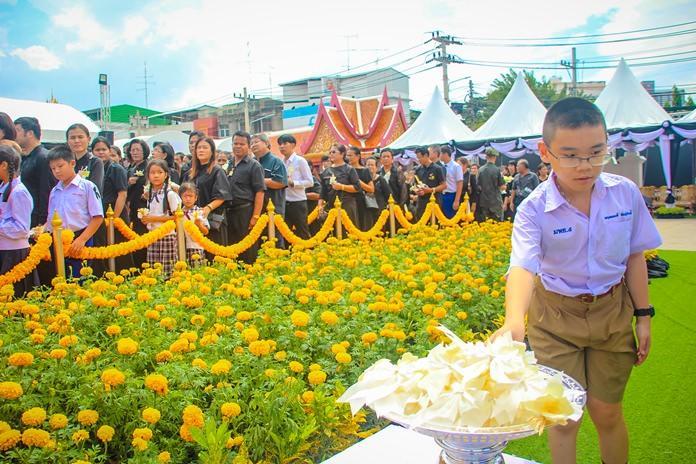 เด็กน้อยวางดอกไม้จันทน์  โดยบรรยากาศพื้นที่โดยรอบ ประดับตกแต่งไปด้วยดอกดาวเรืองเหลืองอร่าม