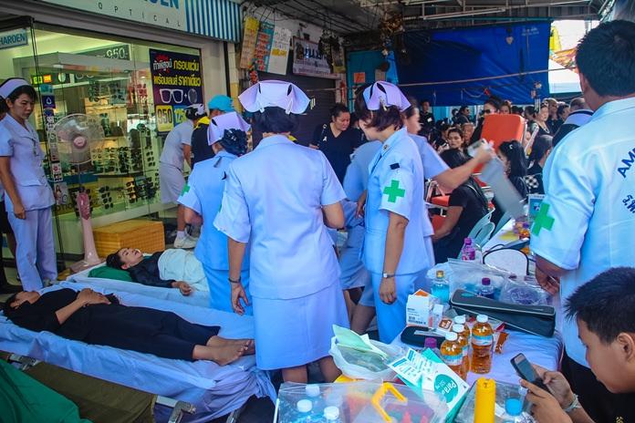 หน่วยปฐมพยาบาล หน้าทางเข้าวัดชัยมงคล พระอารามหลวง กำลังให้การช่วยเหลือประชาชนที่รอจนเป็นลมจำนวนมาก