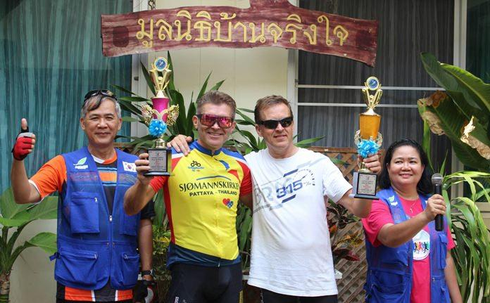 นายสุรกิจ กมลรัตน์ ประธานมูลนิธิบ้านจริงใจ (ซ้าย) นางเพียงตา ชุมน้อย ผู้อำนวยการมูลนิธิบ้านจริงใจ (ขวา) เป็นตัวแทนมอบถ้วยรางวัลให้แก่ผู้ชนะเลิศฝ่ายชาย ในรุ่น 41 กิโลเมตร Mr. Giir Lversen (ที่ 2 จากขวา) และอันดับ 2 Mr.Jeans Over Ravstein (ที่ 2 จากซ้าย)