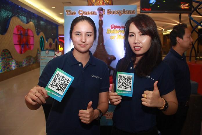 สองสาวสวยพนักงาน  ริบลีส์ เวิลด์ ชู แผ่น คิวอาร์โค๊ด ให้นักท่องเที่ยวและผู้สื่อข่าวที่ร่วมการแถลงทดลองทำตามขั้นตอนเพื่อลุ้นรับรางวัล