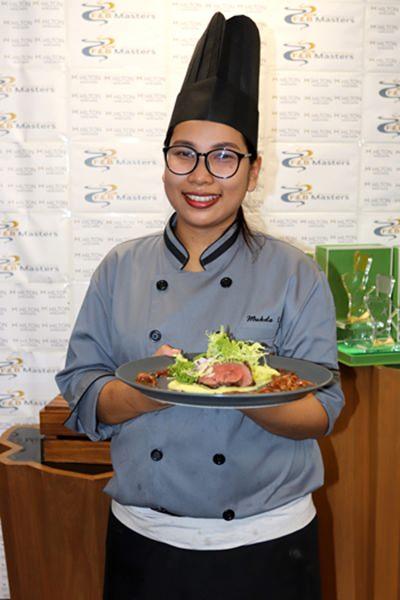 คุณมุกดา อินทร์จันทร์ ตำแหน่งรองหัวหน้าเชฟ จากห้องอาหารและบาร์ฮอไรซัน ชนะเลิศประเภทการแข่งขันทำอาหาร